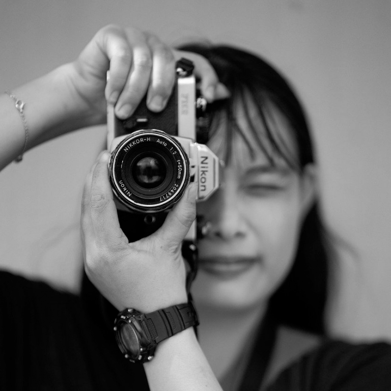 black and white image of a young asian woman taking a photo with a Nikon camera