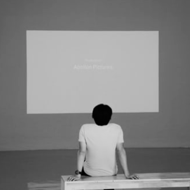 black and white photo of a man looking at a projection on a wall